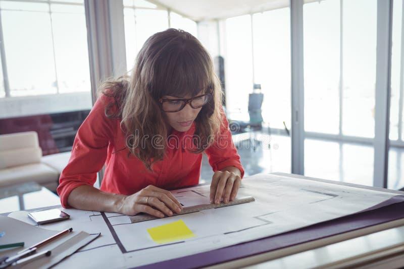 Сфокусированный женский дизайнер по интерьеру работая в офисе стоковое фото rf