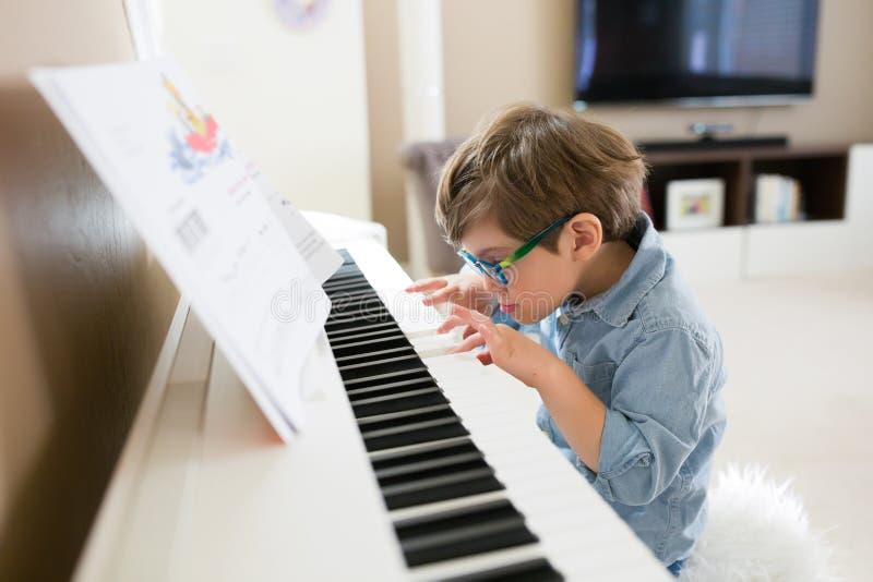 Сфокусированный мальчик малыша играя рояль стоковые фотографии rf