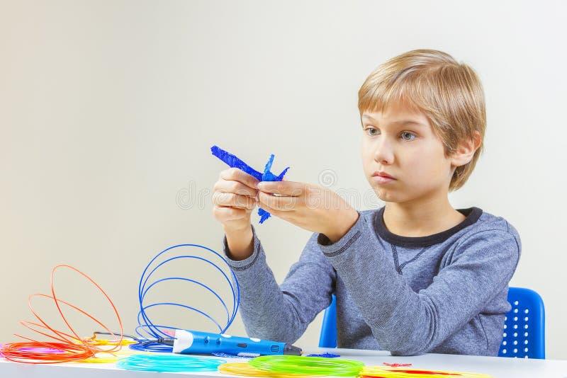 Сфокусированный ребенок при ручка печатания 3d создавая самолет стоковое изображение