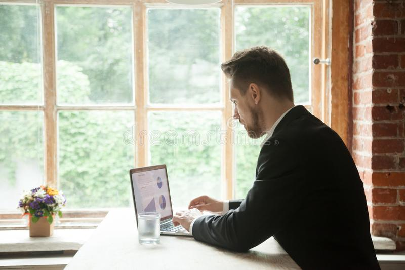 Сфокусированный серьезный бизнесмен работая на компьтер-книжке анализируя проект стоковая фотография