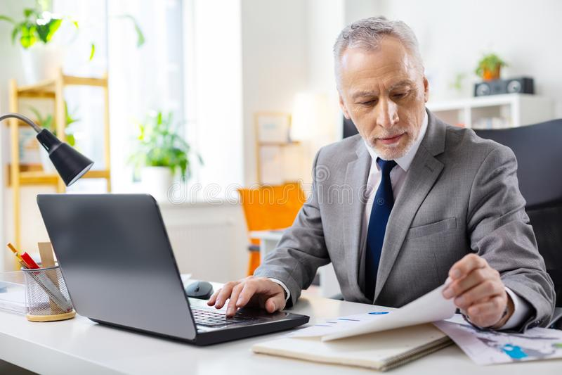 Сфокусированный симпатичный старший человек со стерней проверяя документы стоковое изображение rf
