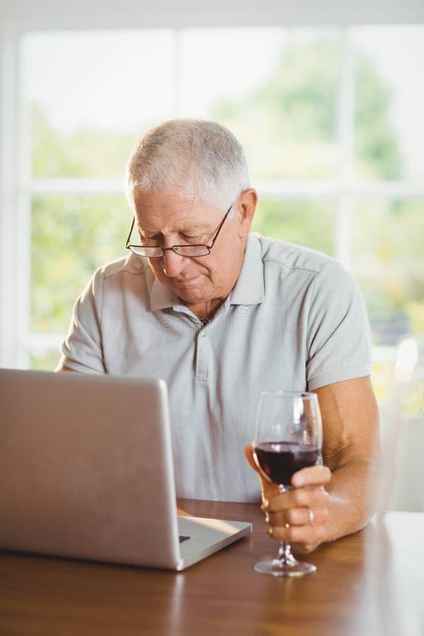 Сфокусированный старший человек используя компьтер-книжку и выпивающ вино стоковое фото rf