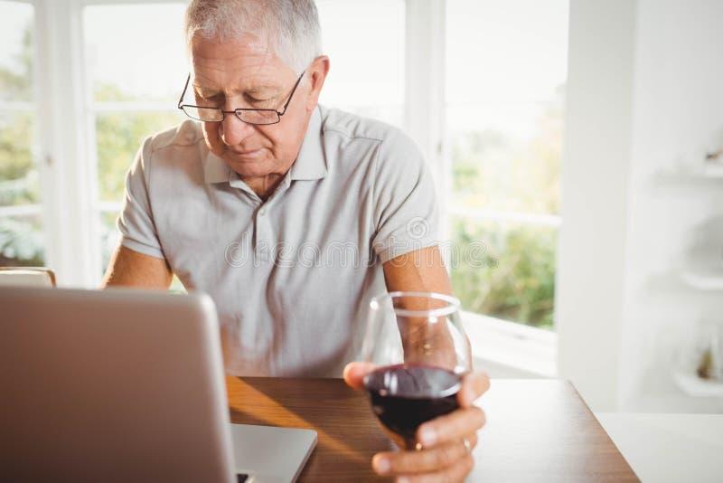 Сфокусированный старший человек используя компьтер-книжку и выпивающ вино стоковое фото