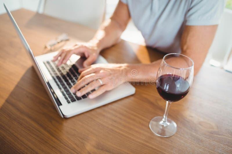 Сфокусированный старший человек используя компьтер-книжку и выпивающ вино стоковые фото