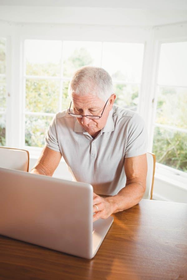 Сфокусированный старший человек используя компьтер-книжку стоковые изображения rf