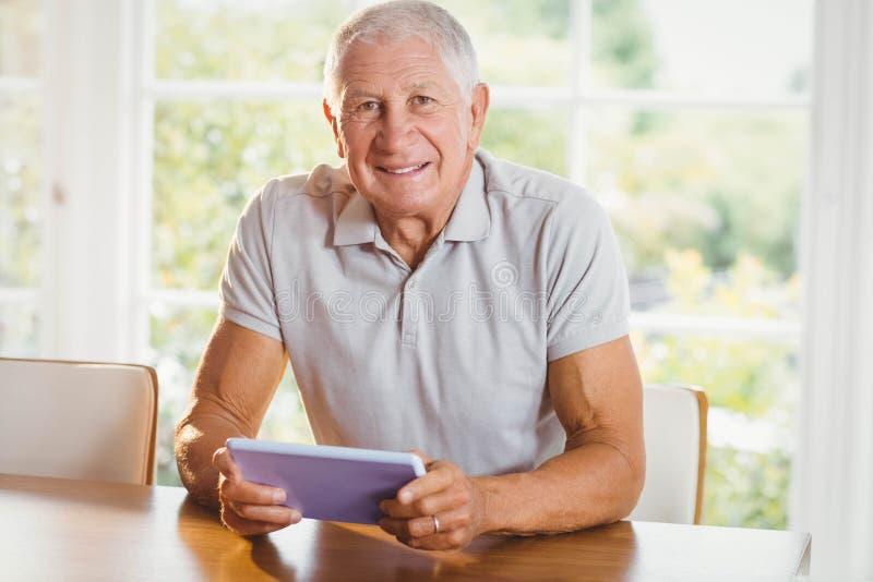 Сфокусированный старший человек используя таблетку стоковое фото rf
