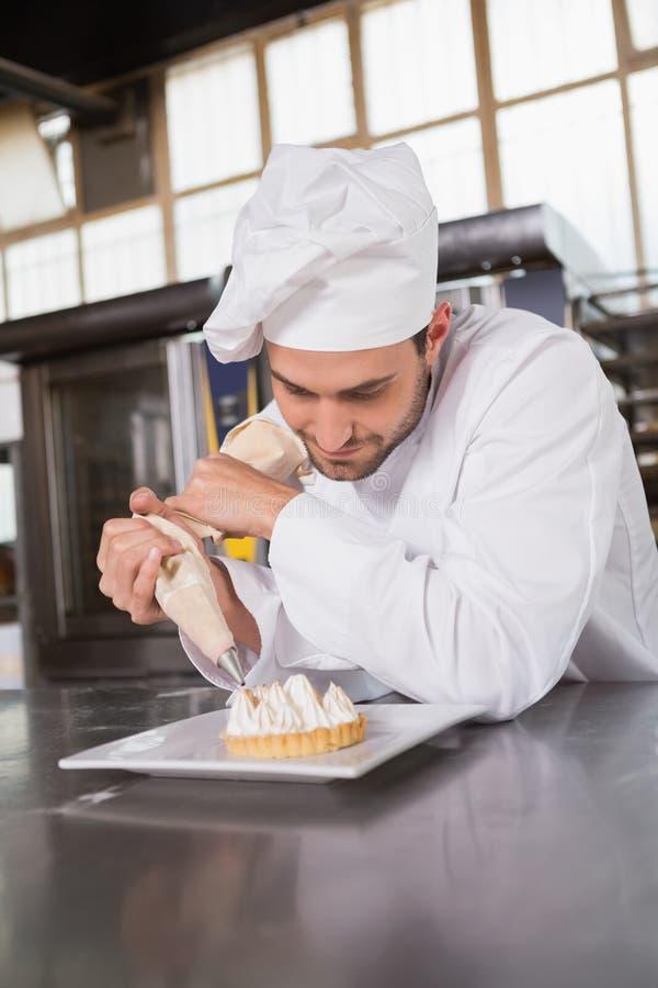 Сфокусированный хлебопек подготавливая handmade торт стоковая фотография