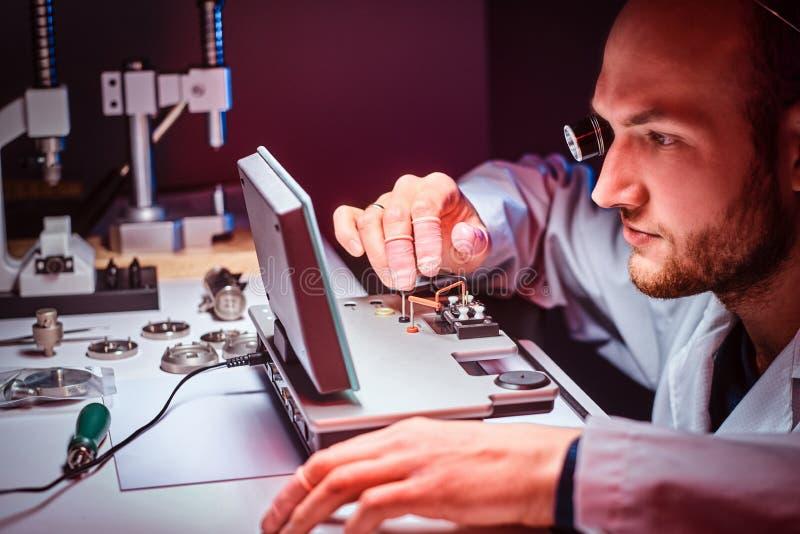 Сфокусированный часовщик работает на его собственной студии стоковая фотография