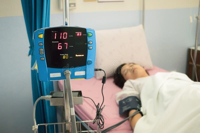 Сфокусируйте на мониторе кровяного давления с пациентом на кровати в больничной палате МЕДИЦИНСКАЯ принципиальная схема стоковая фотография rf