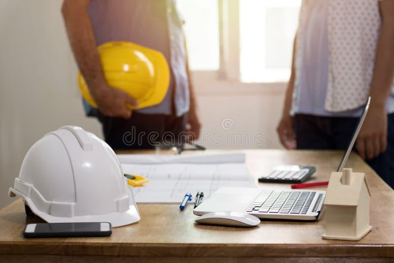 сфокусируйте на safty шлеме на положении работая стола и 2 инженеров стоковые изображения rf