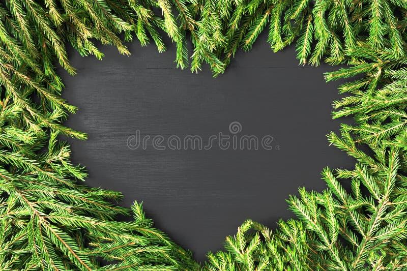Сформированное сердце рамки рождества сделанным естественных ветвей ели на черной деревянной предпосылке Плоское положение, взгля стоковое фото
