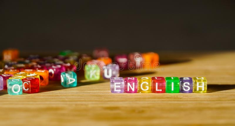 Сформулируйте английский язык от квадрата покрашенных блоков на деревянной поверхности стоковые фото