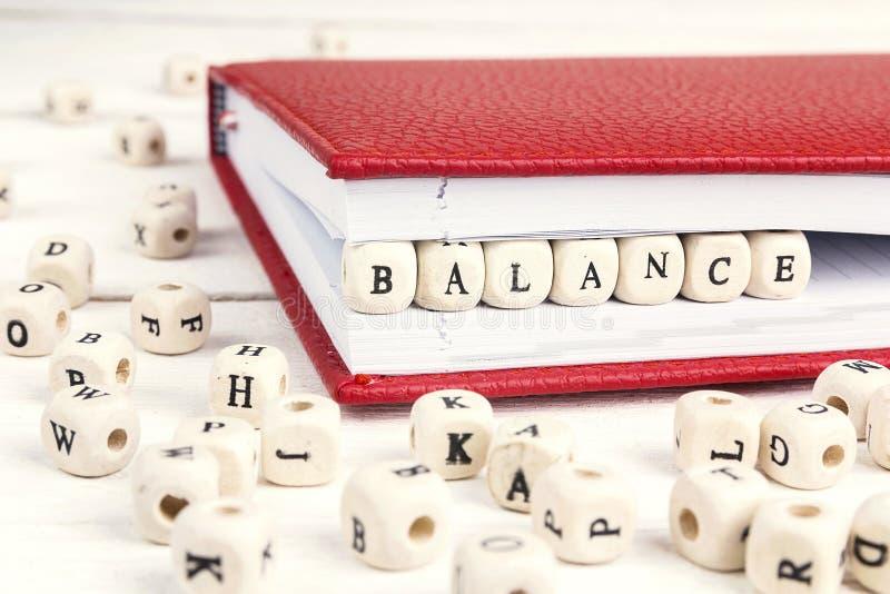 Сформулируйте баланс написанный в деревянных блоках в тетради на белом woode стоковая фотография