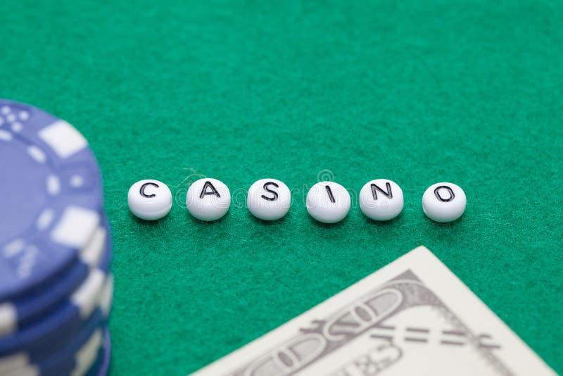 Сформулируйте ` казино ` с обломоками и деньгами покера стоковая фотография