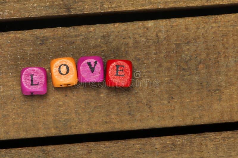 Сформулируйте влюбленность на пестротканых деревянных кубах на древесине стоковые изображения