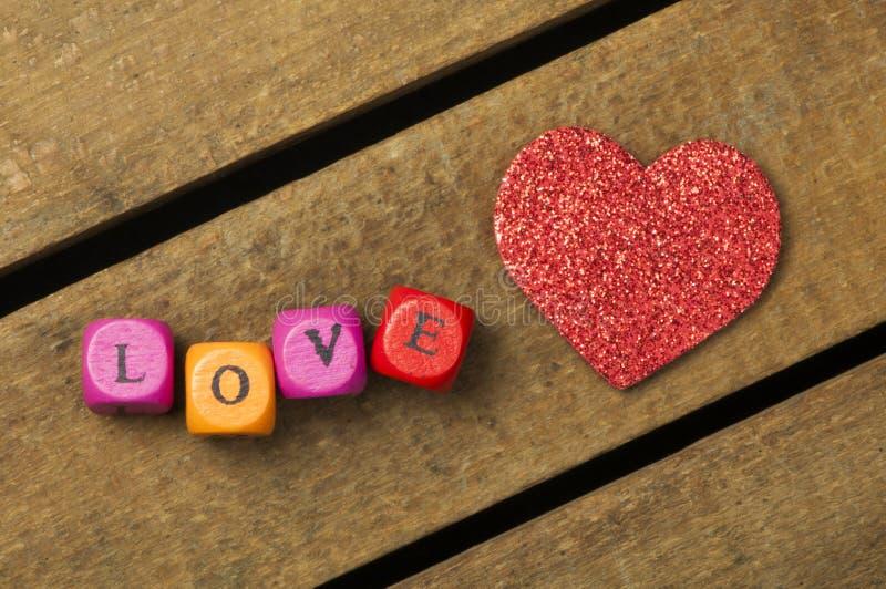 Сформулируйте влюбленность на пестротканых деревянных кубах на деревянной предпосылке стоковые фото