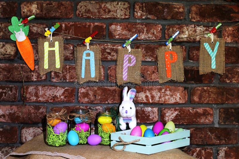 Сформулируйте счастливое на бирках дерюги вися на линии с оранжевой морковью, красочными пасхальными яйцами в опарниках стекла и  стоковое фото