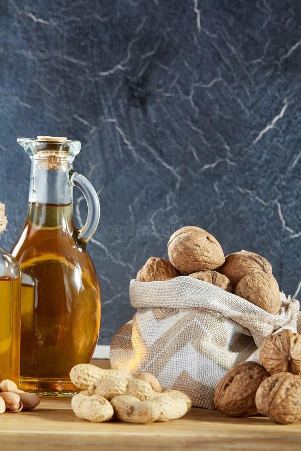 Схематический состав стеклянного масла раздражает с различными видами гаек на деревянном столе, концом-вверх, вертикальным стоковая фотография