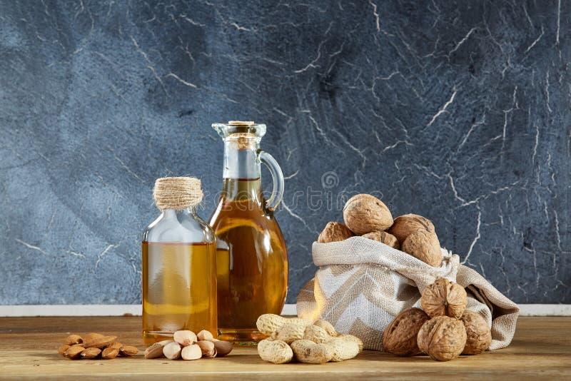Схематический состав стеклянного масла раздражает с различными видами гаек на деревянном столе, концом-вверх стоковые изображения rf