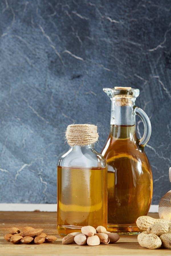 Схематический состав стеклянного масла раздражает с различными видами гаек на деревянном столе, концом-вверх стоковая фотография