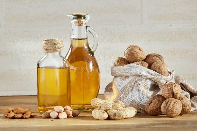 Схематический состав стеклянного масла раздражает с различными видами гаек на деревянном столе, концом-вверх стоковые фотографии rf