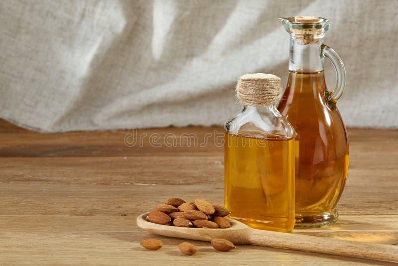 Схематический состав стеклянного масла раздражает с различными видами гаек на деревянном столе, концом-вверх стоковое изображение rf