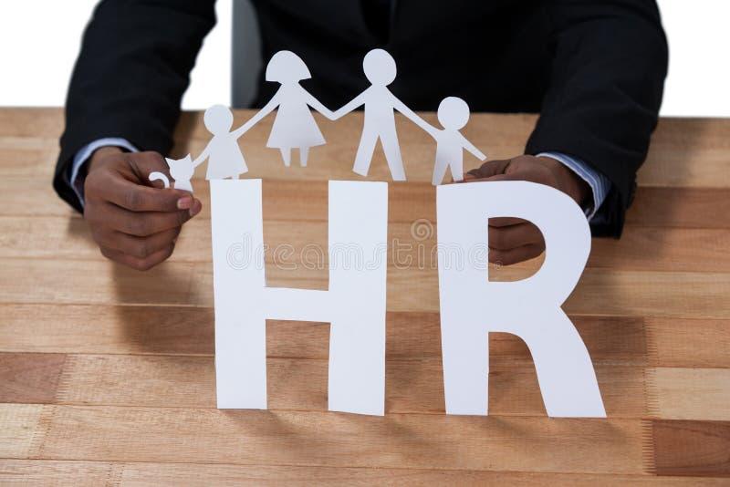 Схематическое изображение бизнесмена держа бумажный figurine выреза на знаке hr стоковое фото