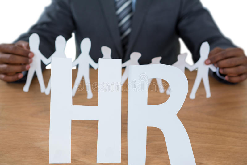 Схематическое изображение бизнесмена держа бумажный figurine выреза на знаке hr стоковые изображения rf