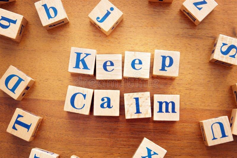 Держите спокойствие Схематическое изображение с текстом сделанным из деревянных кубов стоковая фотография rf