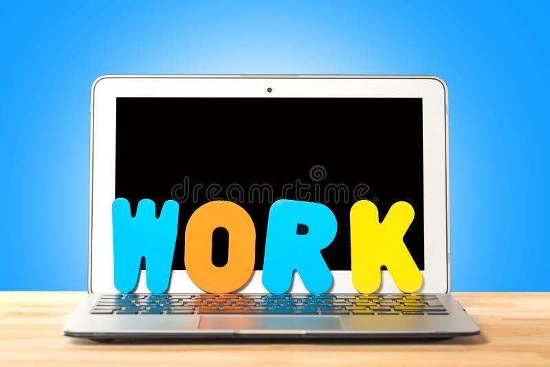 Схематическое место для работы или концепция дела Ноутбук со словом РАБОТОЙ от красочных писем против голубой предпосылки стоковые фотографии rf