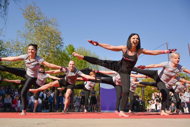 Сход Piloxing группы на открытом воздухе в тренировке парка с инструктором на солнечный весенний день стоковая фотография