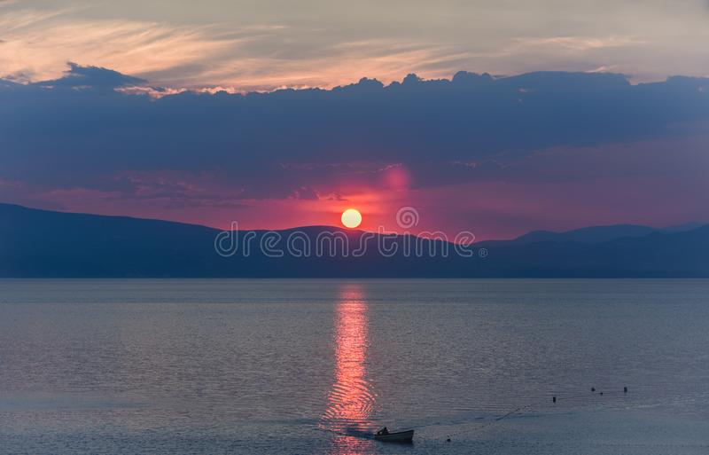 Сценарное озеро с силуэтом шлюпки против гор на заходе солнца, озеро Ohrid, Македония стоковые изображения rf