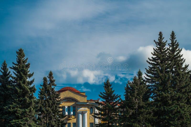 Сценарное солнечное небо с brights заволакивает с восточными соснами и зданием шутовства в общественном имуществе ботанического с стоковые изображения