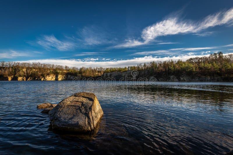 Сценарное фото затопленного карьера близко с темно-синим небом и белыми облаками стоковые фото