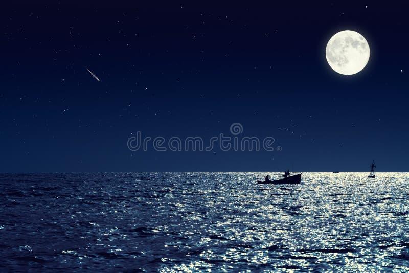 Сценарный взгляд малой рыбацкой лодки в морской воде штиля на море на ноче и стоковое фото