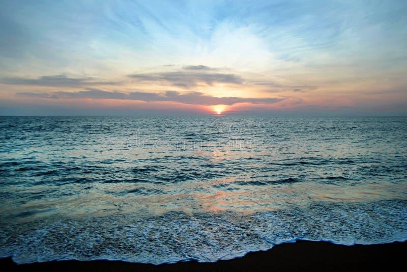 Сценарный взгляд на море и песок приставают к берегу с красочным заходом солнца стоковые изображения rf
