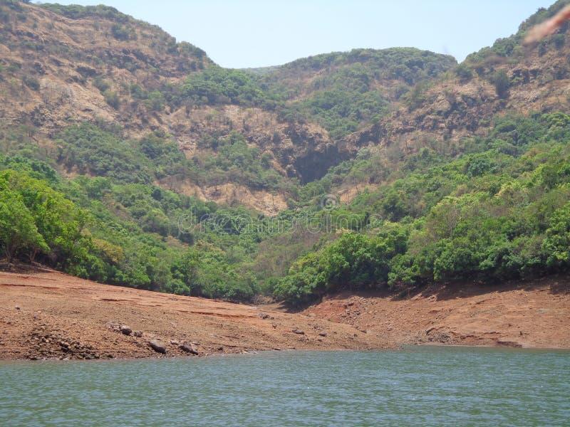 Сценарный взгляд подпора реки в холмах и растительности гор стоковое фото rf