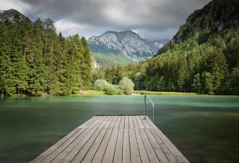 Сценарный взгляд plansarsko озера горы с деревянным footbridge в долгой выдержке, Словенией стоковая фотография