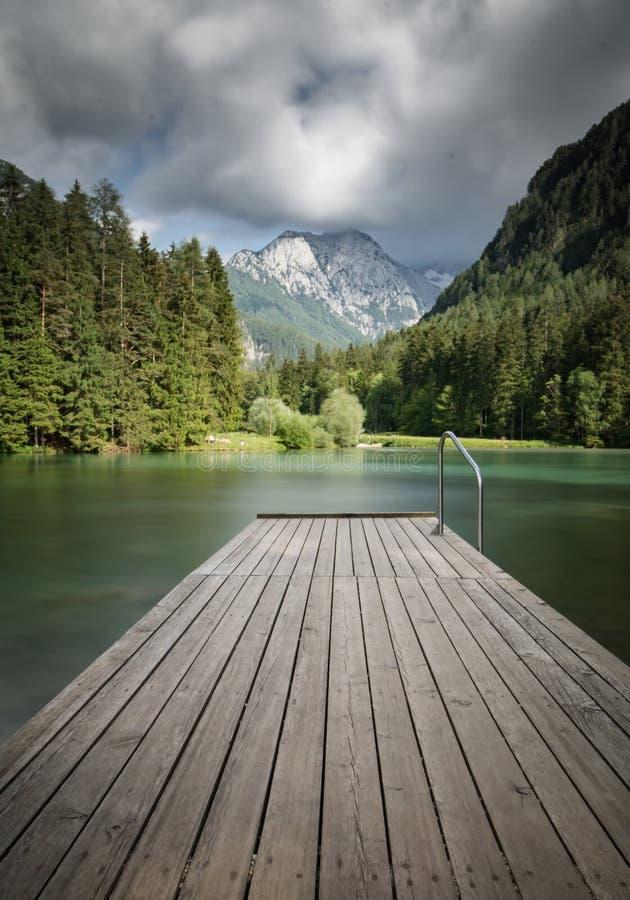 Сценарный взгляд plansarsko озера горы с деревянным footbridge в долгой выдержке, Словенией стоковое фото