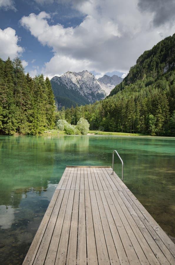 Сценарный взгляд plansarsko озера горы с деревянным footbridge, Словенией стоковые изображения