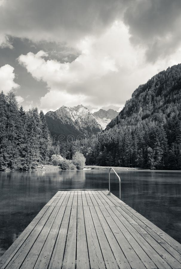 Сценарный взгляд plansarsko озера горы с деревянным footbridge, Словенией стоковая фотография