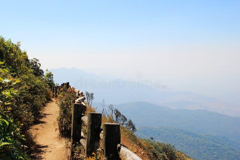 Сценарный взгляд с следом, деревянной загородкой и горами на предпосылке стоковые изображения