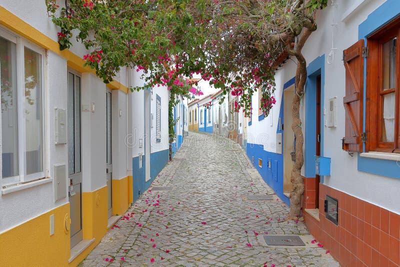 Сценарный вымощенный переулок с красочными домами и цветками в рыбацком поселке Ferragudo, Алгарве стоковое фото