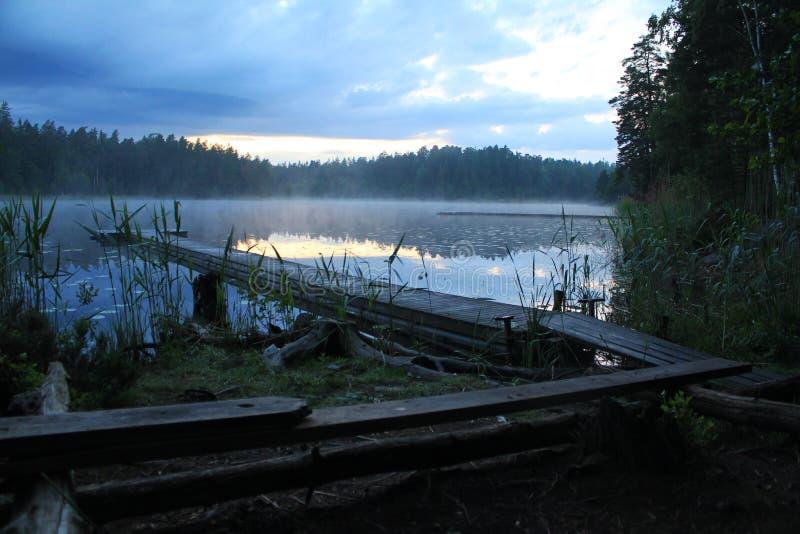 Сценарный и идилличный ландшафт озера с деревянными footbridge и туманом на вечере sommer стоковые фото