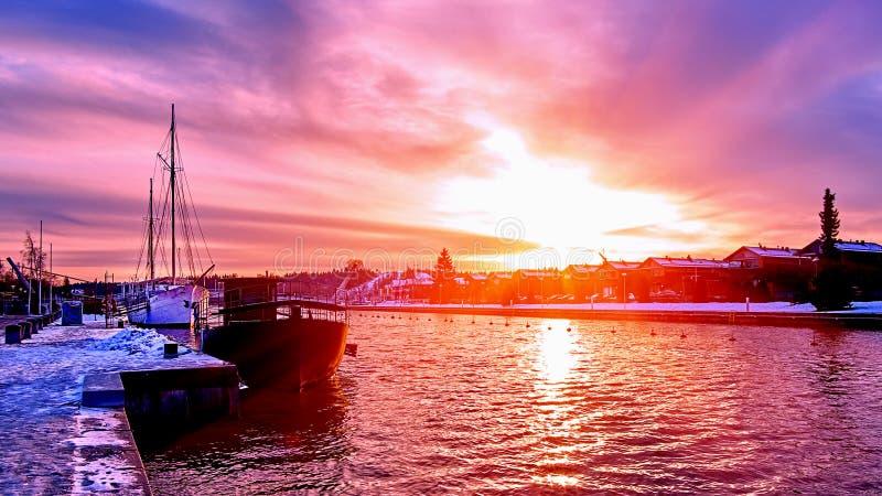 Сценарный красный заход солнца пурпура и фиолетовых над рекой сельской местности в Европе со старыми кораблями имея остатки на сн стоковые фотографии rf