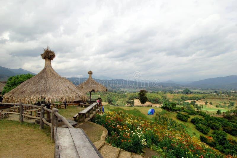 Сценарный ландшафт на горах, малой деревне, шатрах и поле красочных хризантем стоковое фото rf