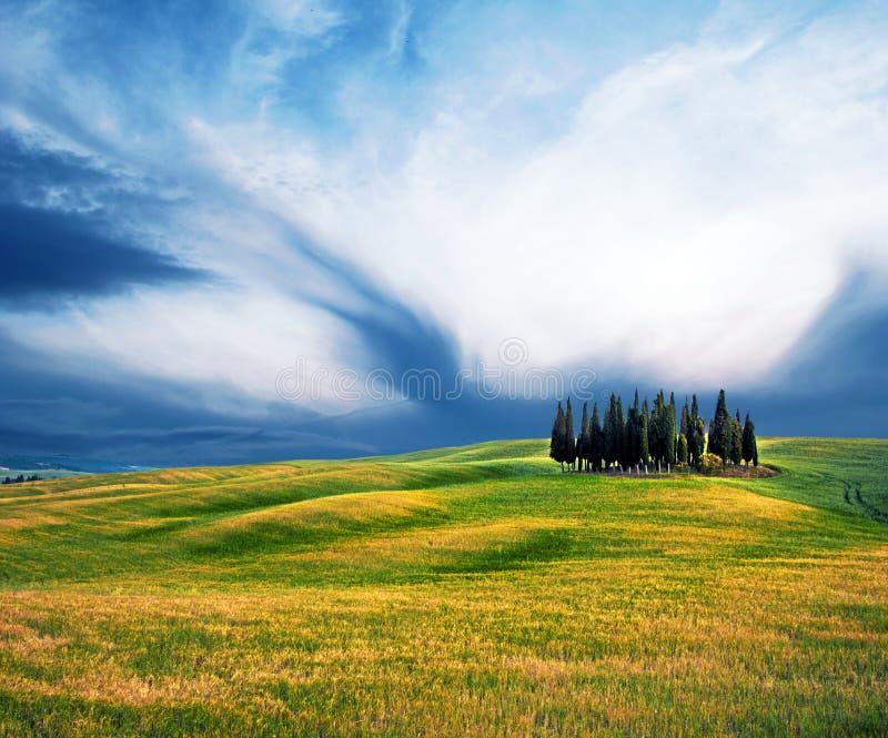 """Сценарный ландшафт с холмами против облаков в Val d """"Orcia, Тоскане, Италии Чудесные места стоковое фото"""