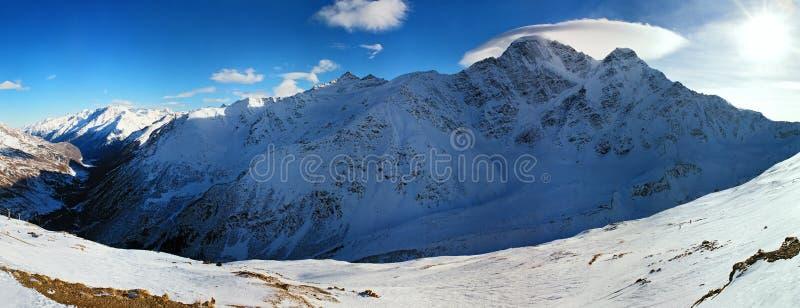 Сценарный панорамный ландшафт зимы снежной горной цепи Кавказа с пиками и облаками на день голубого неба солнечный Elbrus, Cheget стоковое изображение