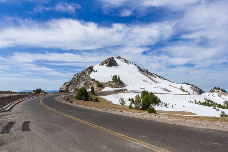 Сценарный привод оправы шоссе с предпосылкой пика наблюдателя скалистой горы в национальном парке озера кратер стоковое фото rf