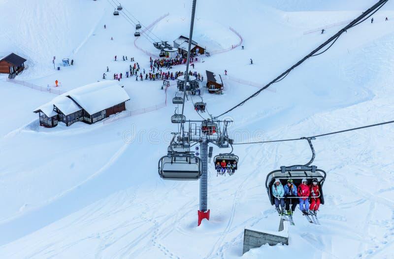 Сценарный солнечный ландшафт зимы лыжников и пансионеров ехать на следах лыжи и подъем лыжи стула на лыжном курорте горы Gorky Go стоковое фото